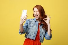 Concept de mode de vie : Jeune femme gaie posant tout en se photographiant sur l'appareil-photo futé de téléphone pour une causer Images libres de droits