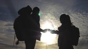 Concept de navigation de tourisme de travail d'?quipe Les randonneurs heureux de famille silhouettent en nature regardant dans un clips vidéos