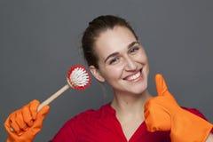 Concept de nettoyage d'amusement pour la fille espiègle tenant une brosse de plat Photographie stock libre de droits