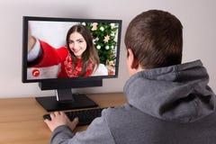 Concept de Noël - équipez videochatting avec son amie Photo stock