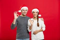 Concept de Noël - beau jeune couple de portrait montrant le geste correct avec le doigt à l'appareil-photo Images libres de droits