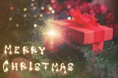 Concept de Noël cadeau rouge avec le Joyeux Noël fait par des étincelles Photos stock