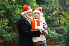 Concept de Noël et de personnes - équipez donner un cadeau de boîte à une femme Images libres de droits