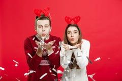Concept de Noël - homme heureux et femme caucasiens dans des chapeaux de renne célébrant Noël grillant avec des cannelures de cha Images libres de droits