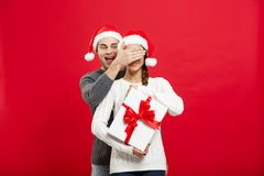Concept de Noël - jeune ami beau dans la surprise de chandail son amie avec le cadeau blanc Photos libres de droits