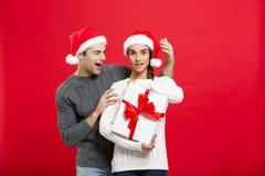 Concept de Noël - jeune ami beau dans la surprise de chandail son amie avec le cadeau blanc Photo libre de droits