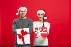 Concept de Noël - jeune couple attrayant donnant des cadeaux célébrant entre eux dans le jour de Noël Photos libres de droits