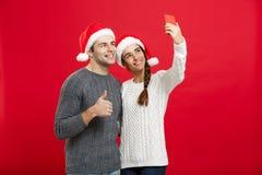 Concept de Noël - jeune couple attrayant prenant un selfie par le téléphone portable célébrant dans le jour de Noël Photos stock