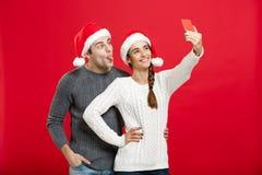 Concept de Noël - jeune couple attrayant prenant un selfie par le téléphone portable célébrant dans le jour de Noël Photos libres de droits