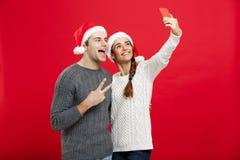 Concept de Noël - jeune couple attrayant prenant un selfie par le téléphone portable célébrant dans le jour de Noël Image stock
