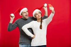 Concept de Noël - jeune couple attrayant prenant un selfie par le téléphone portable célébrant dans le jour de Noël Images libres de droits