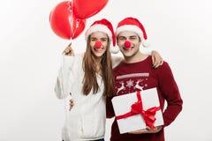 Concept de Noël - jeune couple caucasien jugeant des cadeaux, le champnage et le ballon faisant le visage drôle sur Noël Images stock