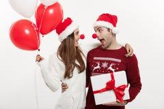 Concept de Noël - jeune couple caucasien jugeant les cadeaux, le champagne et le ballon faisant le visage drôle sur Noël Photos libres de droits