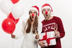 Concept de Noël - jeune couple caucasien jugeant les cadeaux, le champagne et le ballon faisant le visage drôle sur Noël Photo libre de droits