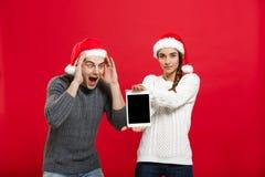 Concept de Noël - jeune couple heureux dans des chandails de Noël étonnants quelque chose dans le comprimé numérique Image libre de droits