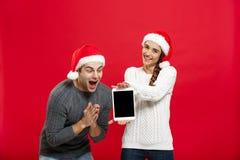 Concept de Noël - jeune couple heureux dans des chandails de Noël étonnants quelque chose dans le comprimé numérique Photographie stock libre de droits