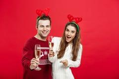 Concept de Noël - jeune couple heureux dans des chandails célébrant Noël avec Champagne Photo libre de droits
