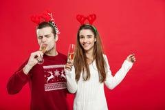Concept de Noël - jeune couple heureux dans des chandails célébrant Noël avec Champagne Photos stock