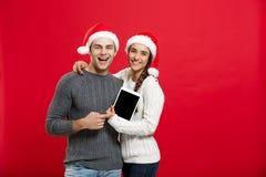 Concept de Noël - jeune couple heureux dans des chandails de Noël tenant le comprimé numérique Photos stock