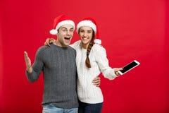Concept de Noël - jeune couple heureux dans des chandails de Noël tenant le comprimé numérique Photos libres de droits