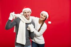 Concept de Noël - jeune couple heureux dans le sweatesr célébrant Noël avec jouer et danser Photographie stock libre de droits