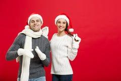 Concept de Noël - jeune couple heureux dans le sweatesr célébrant Noël avec jouer et danser Photos stock