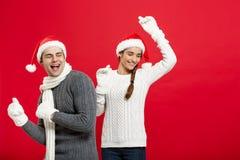 Concept de Noël - jeune couple heureux dans le sweatesr célébrant Noël avec jouer et danser Images stock
