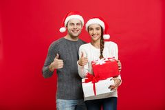 Concept de Noël - jeune couple de portrait dans le chandail de Noël montrant le coup avec des cadeaux Photos stock