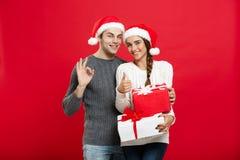 Concept de Noël - jeune couple de portrait dans le chandail de Noël montrant le geste correct avec des cadeaux Image libre de droits
