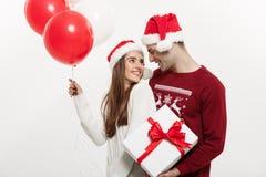 Concept de Noël - la jeune amie tenant le ballon étreint Image stock