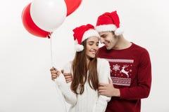 Concept de Noël - la jeune amie tenant le ballon est étreignante et jouante avec son ami faisant une surprise dessus Photographie stock libre de droits