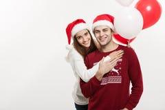 Concept de Noël - la jeune amie tenant le ballon est étreignante et jouante avec son ami faisant une surprise dessus Photos stock