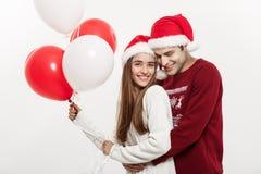 Concept de Noël - la jeune amie tenant le ballon est étreignante et jouante avec son ami faisant une surprise dessus Image stock