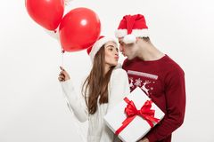 Concept de Noël - la jeune amie tenant le ballon est étreignante et jouante avec son ami faisant une surprise dessus Photo stock