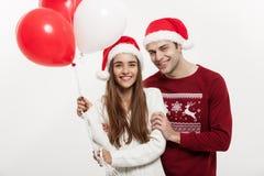 Concept de Noël - la jeune amie tenant le ballon est étreignante et jouante avec son ami faisant une surprise dessus Photographie stock