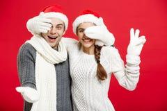 Concept de Noël - les jeunes couples élégants heureux dans des vêtements d'hiver ferment des yeux chaque autres qui célèbrent dan Image stock