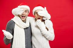 Concept de Noël - les jeunes couples élégants heureux dans des vêtements d'hiver ferment des yeux chaque autres qui célèbrent dan Photographie stock
