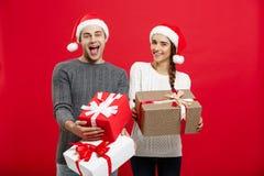 Concept de Noël - les jeunes couples attrayants tenant beaucoup de présents ont plaisir à faire des emplettes et célébrer dans le Image stock