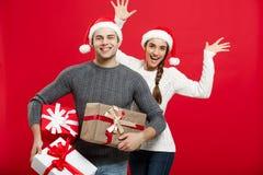 Concept de Noël - les jeunes couples attrayants tenant beaucoup de présents ont plaisir à faire des emplettes et célébrer dans le Photo stock