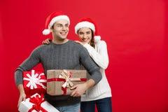 Concept de Noël - les jeunes couples attrayants tenant beaucoup de présents ont plaisir à faire des emplettes et célébrer dans le Images libres de droits