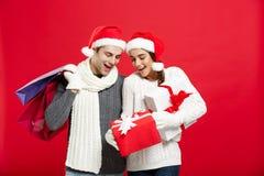 Concept de Noël - les jeunes couples attrayants tenant le panier ont plaisir à faire des emplettes et célébrer dans le jour de No Image stock