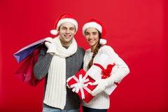 Concept de Noël - les jeunes couples attrayants tenant le panier ont plaisir à faire des emplettes et célébrer dans le jour de No Images stock