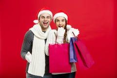 Concept de Noël - les jeunes couples attrayants tenant le panier ont plaisir à faire des emplettes et célébrer dans le jour de No Photo stock