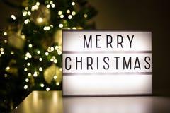 Concept de Noël - lihtbox avec des mots de Joyeux Noël dans r foncé photographie stock libre de droits