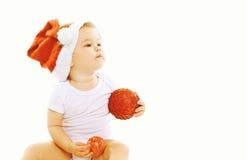 Concept de Noël - petit enfant dans le chapeau rouge de Santa avec des boules de Noël Photographie stock
