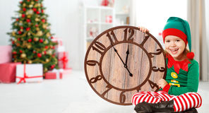 Concept de Noël Petit enfant dans le costume Elf avec l'horloge Image libre de droits