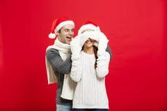 Concept de Noël - portrait d'une amie étonnante de jeune ami romantique au-dessus de fond rouge de studio Image stock