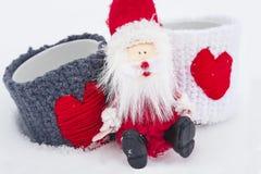 Concept de Noël Santa Claus s'assied sur la neige avec deux tasses d'amour Noël et la nouvelle année viennent Photos stock
