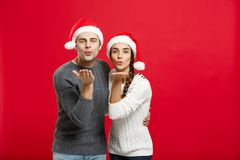 Concept de Noël - souhait de soufflement de beaux couples de portrait à l'appareil-photo dans le jour de Noël Image libre de droits