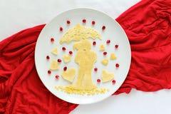Concept de nourriture d'art Silhouette d'un couple dans l'amour sous le parapluie Crêpes de dentelle avec des graines de grenade Photographie stock libre de droits